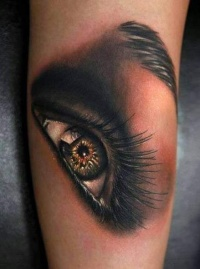 Colorful women eye tattoo on arm