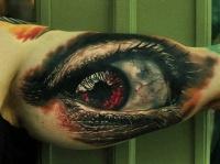 Dreadful red eye tattoo on arm