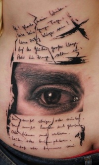 Eye and text tattoo on ribs