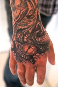 Snake eyes tattoo on the hand by graynd